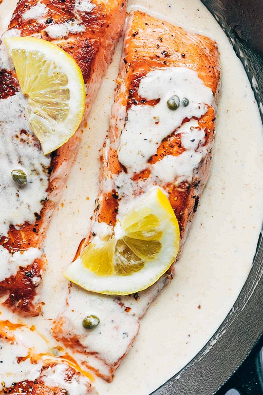 Close up of creamy salmon piccata with lemon sauce on top in a pan