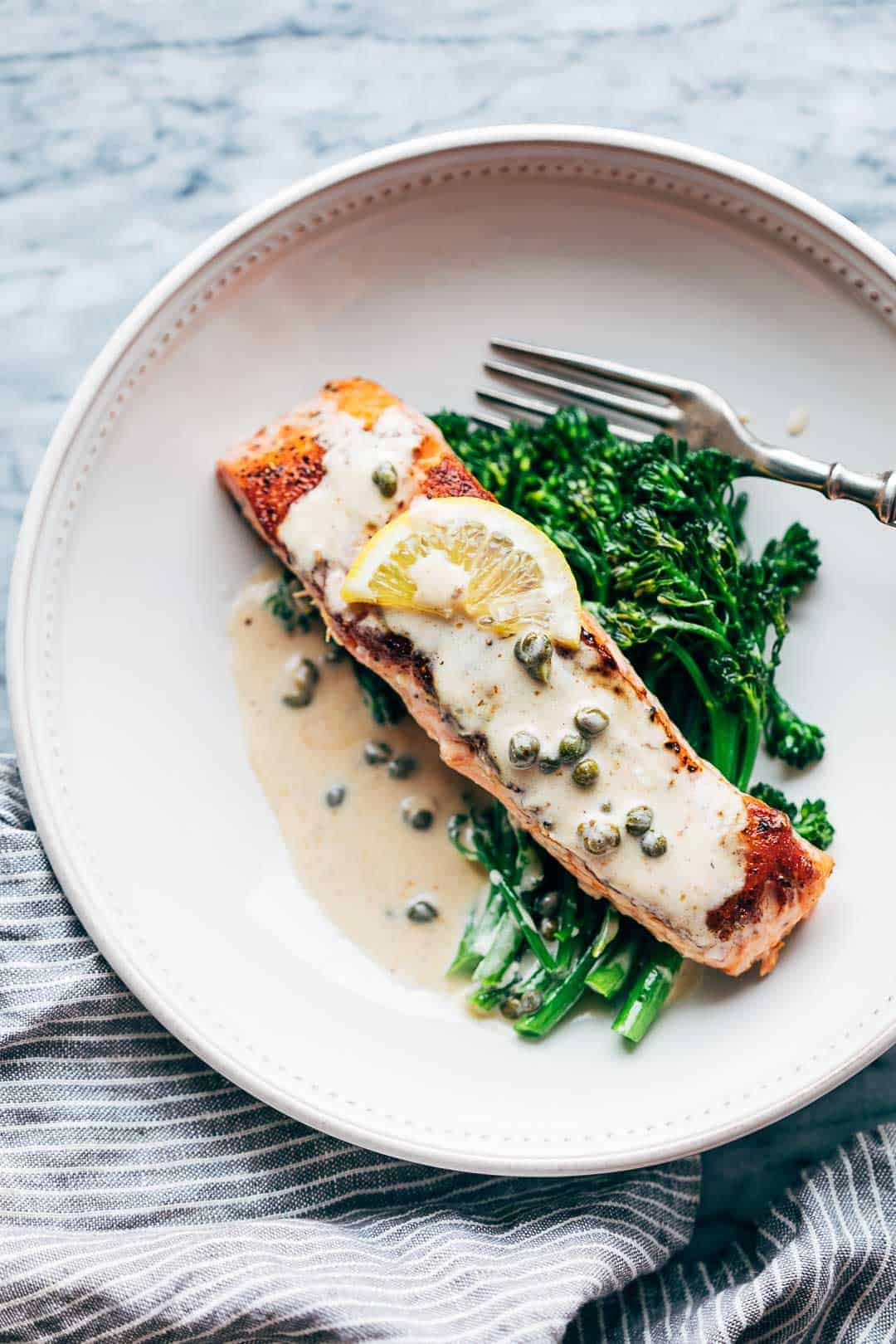 Creamy salmon piccata with lemon butter sauce served with steamed broccolini in a white bowl