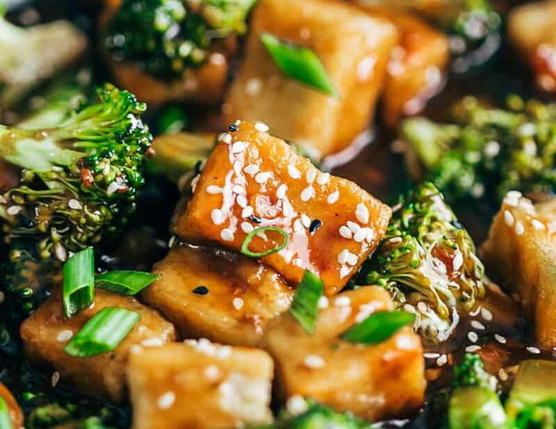 Closeup of crispy tofu broccoli stir fry garnished with toasted sesame seeds and spring onions.
