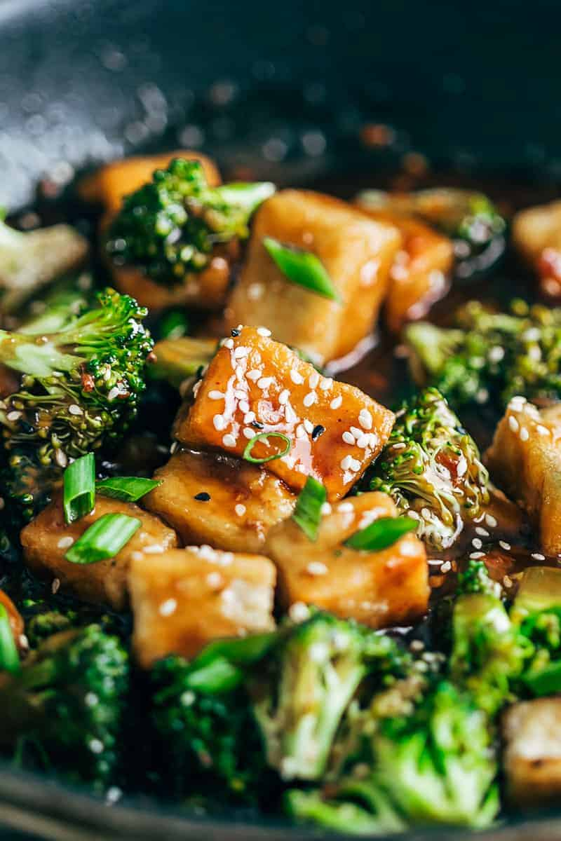 Closeup of crispy tofu broccoli stir fry garnished with toasted sesame seeds and spring onions