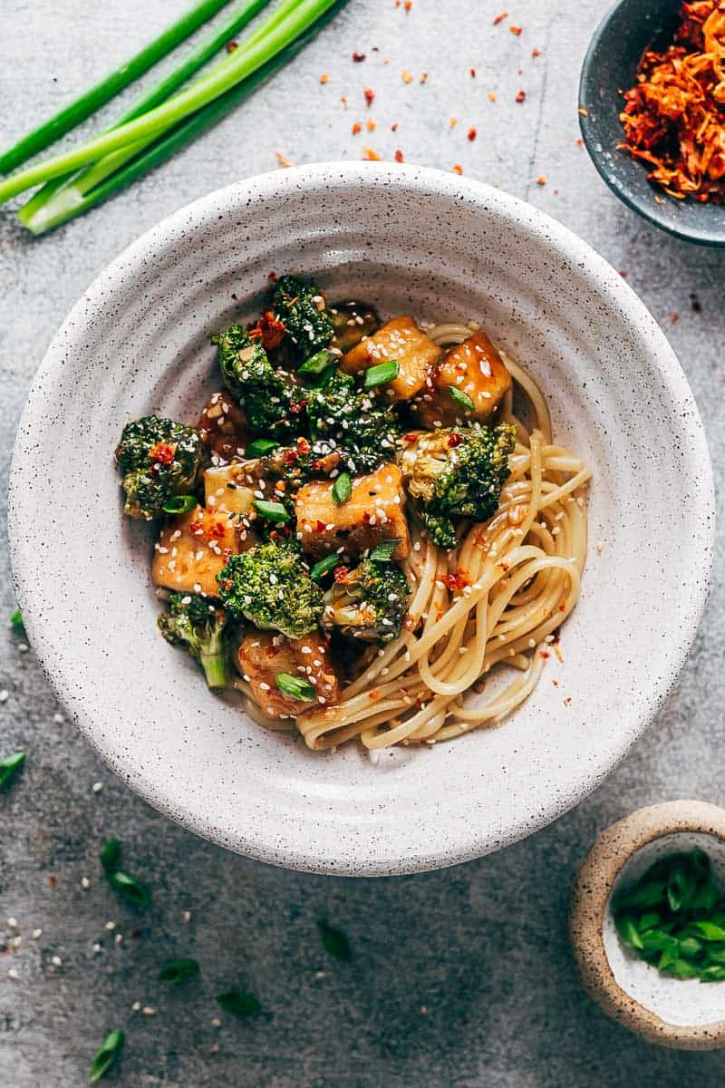 Crispy tofu broccoli stir fry in a white bowl topped with chilli flakes, green onions and sesame seeds