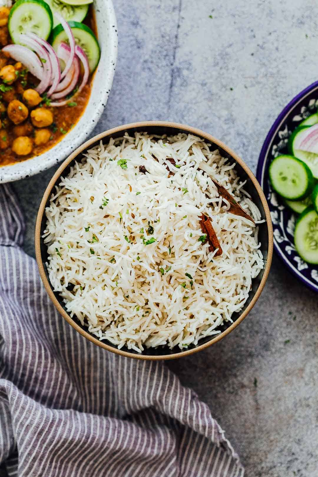 Jeera Rice served in a bowl with curry and salad on the side