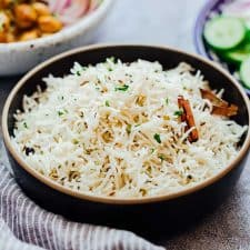 Steamed jeera rice served fresh in a black bowl with a side of Indian curry.