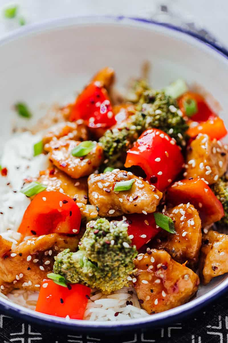 Easy teriyaki chicken with broccoli and bell peppers served in a white bowl over steamed rice and topped with sesame seeds and green onions