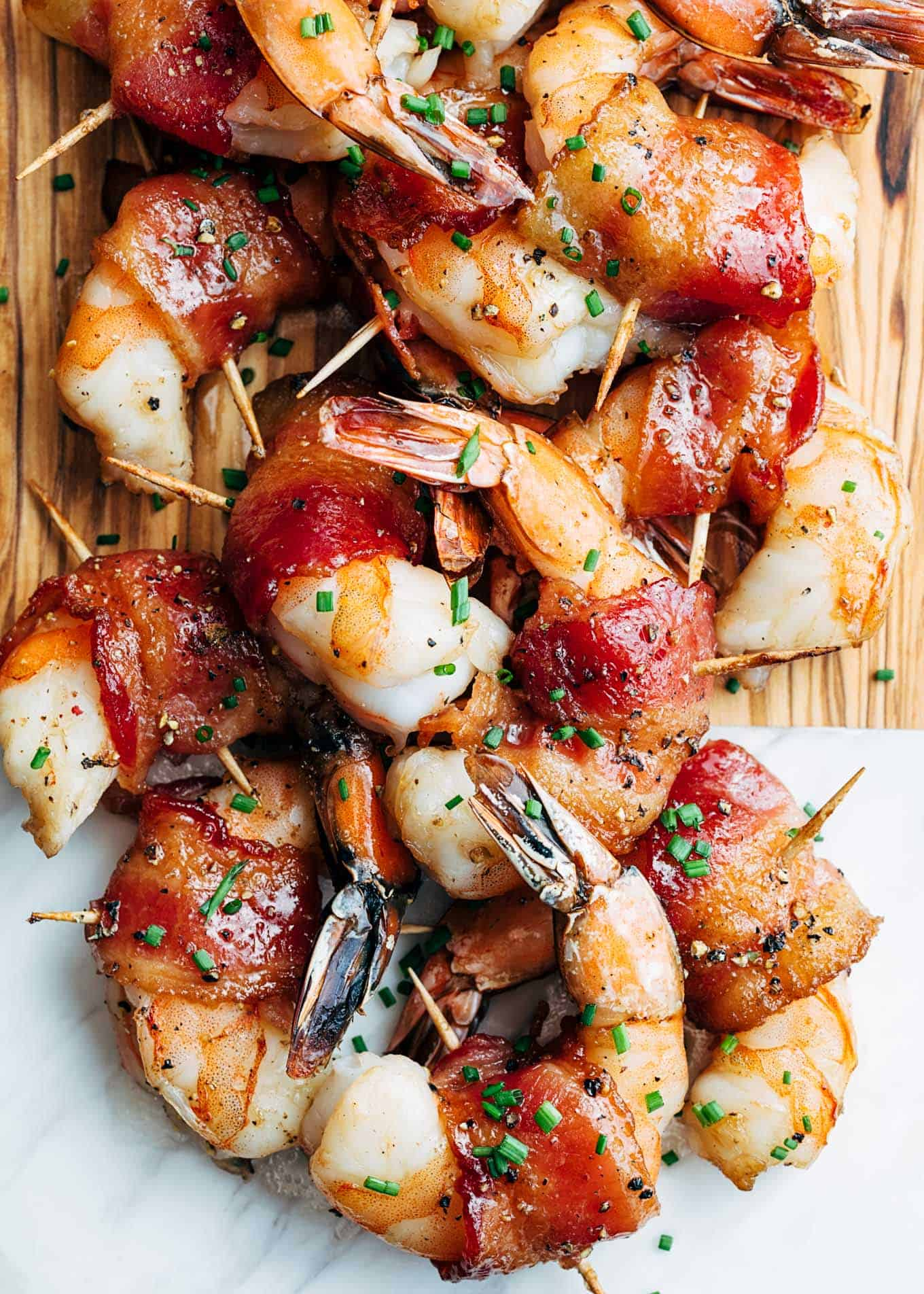 Bacon wrapped shrimp piled on a marble wooden serving board with toothpicks in them