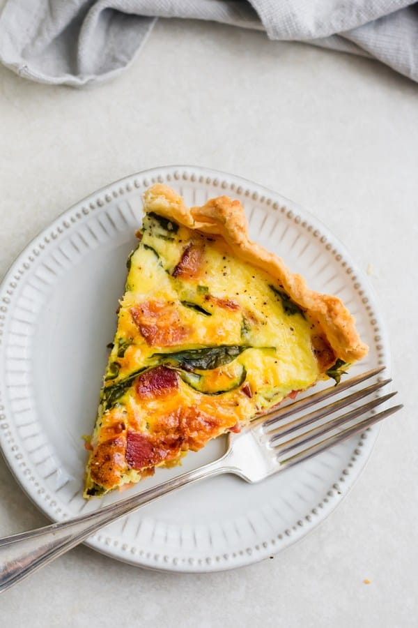 A slice of breakfast quiche on a white plate - one of the bacon recipes