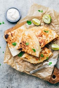Chicken Fajita Quesadillas served on a wooden board with sour cream, lime wedges and fresh cilantro