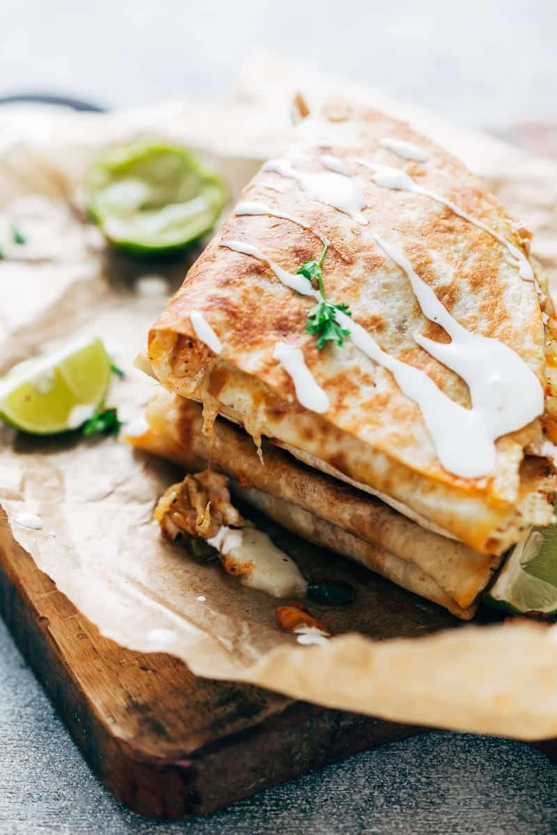 Closeup of chicken fajita quesadillas with sour cream drizzled on top