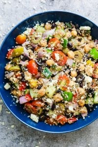 Mediterranean quinoa salad served in a blue bowl sprinkled with crumbled feta