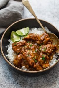Slow cooker chicken curry served over steamed rice in a black bowl with lemon wedges