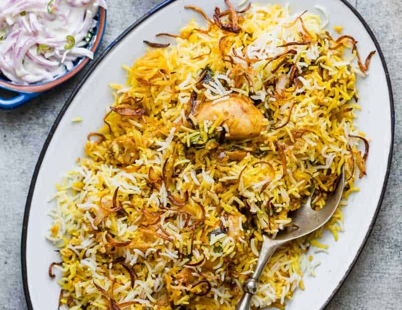 Chicken Biryani served on a platter with crispy fried onions and onion raita.