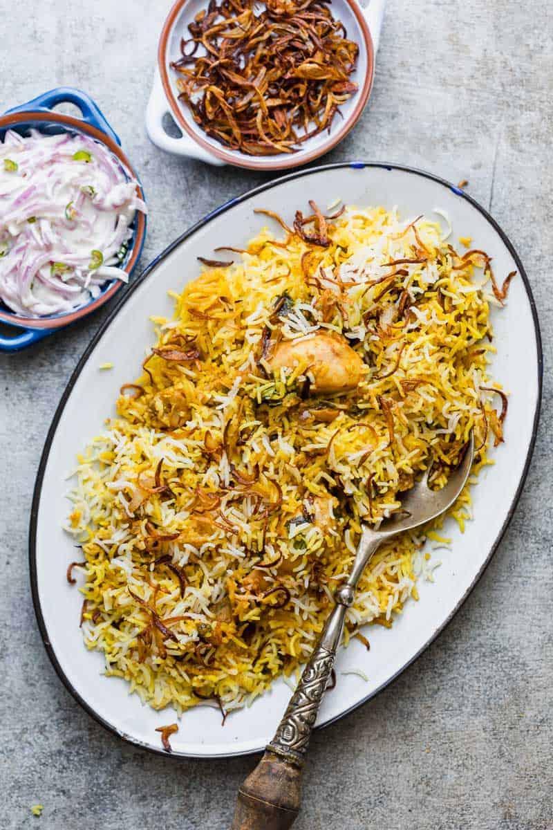 Chicken Biryani served on a platter with crispy fried onions and onion raita