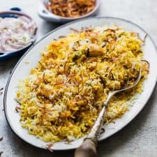 Chicken Biryani served on a platter with crispy fried onions and onion raita.