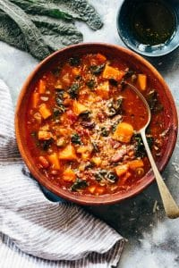 Winter Vegetarian Minestrone Soup served in a bowl topped with parmesan and olive oil
