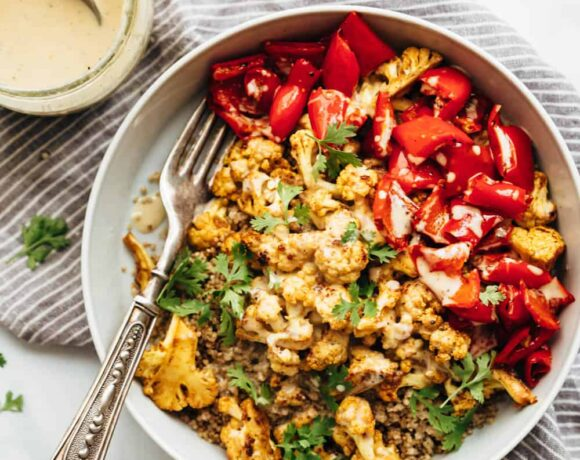 Curried roasted cauliflower bowl with tahini dressing drizzled on top