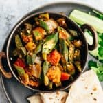 Overhead shot of bhindi masala served with chapatis and salad
