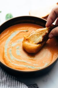 Roasted Tomato Pesto Soup served in a bowl with cheesy bread being dunked into soup