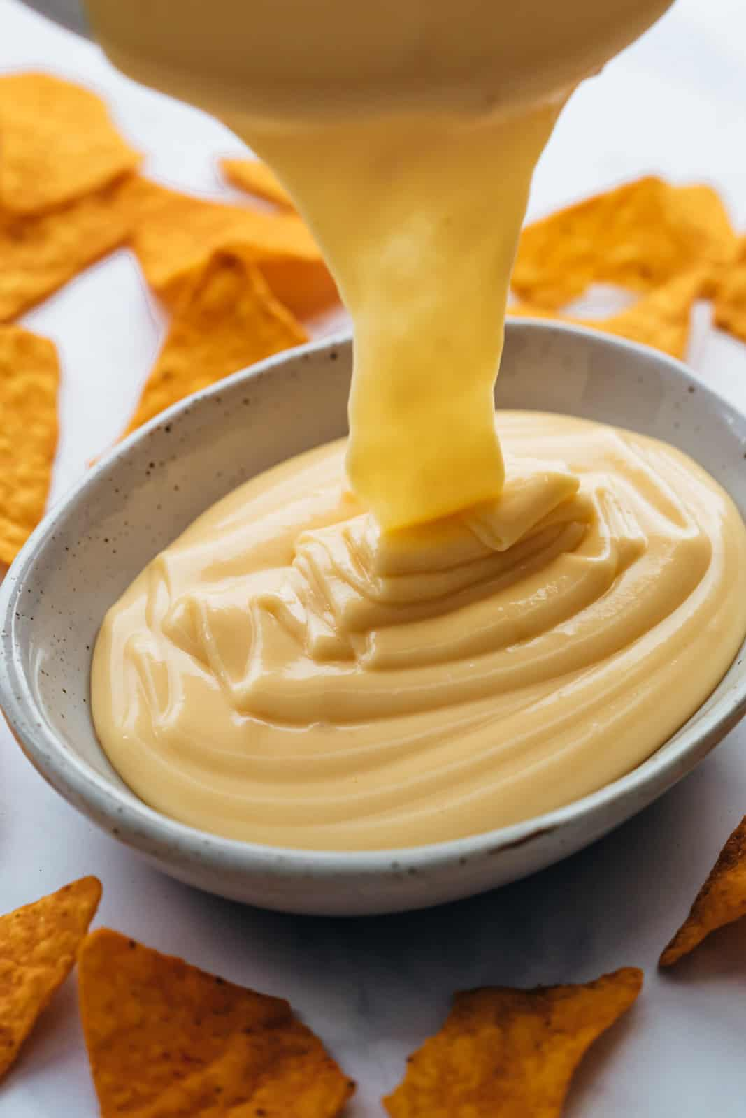 Pouring nacho cheese sauce into a serving dip bowl