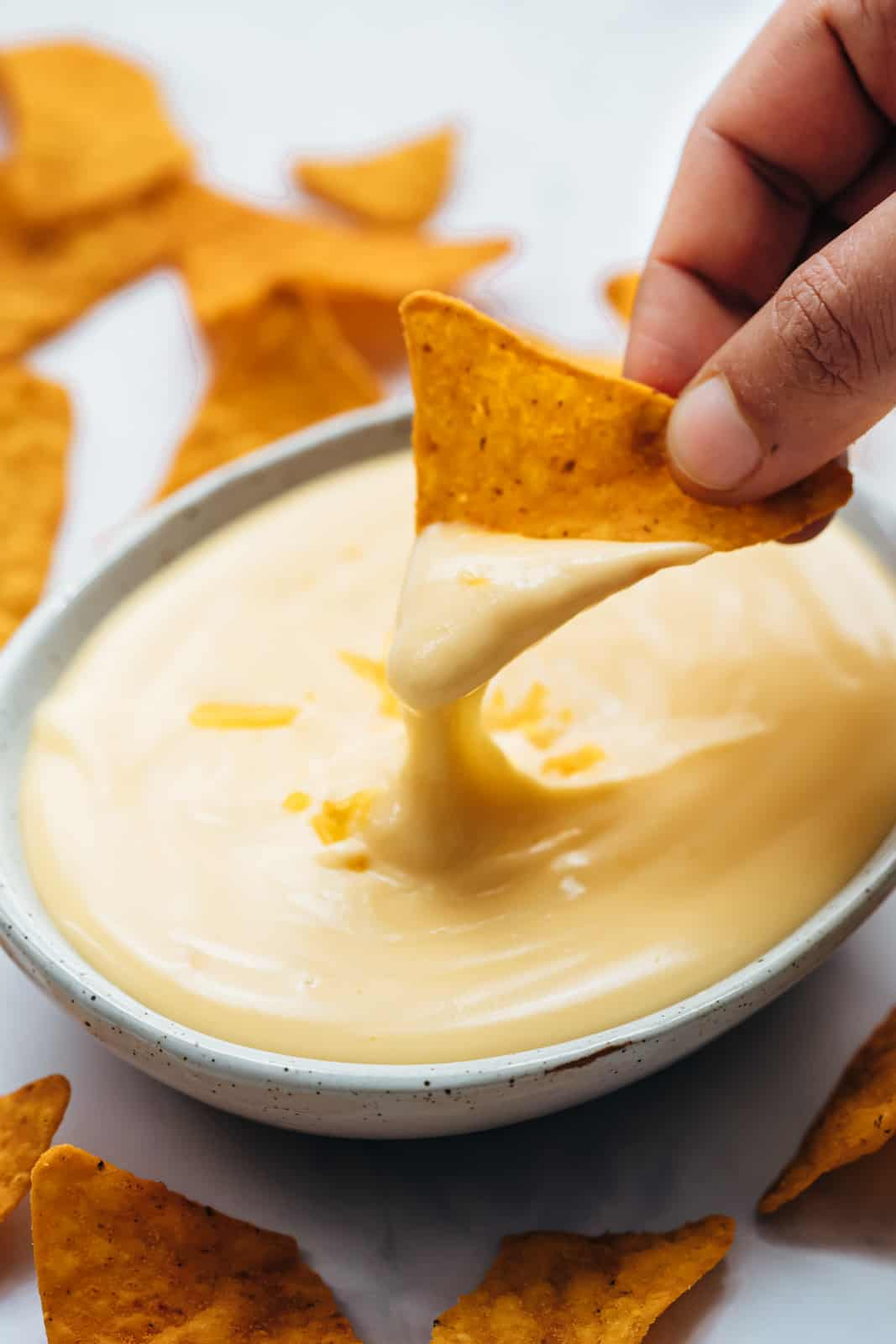 Dipping nacho into cheese sauce