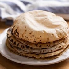 Soft puffy rotis stacked on a plate