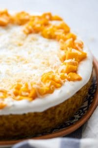 Eggless Mango cake topped with whipped cream and fresh mangoes and served on a platter