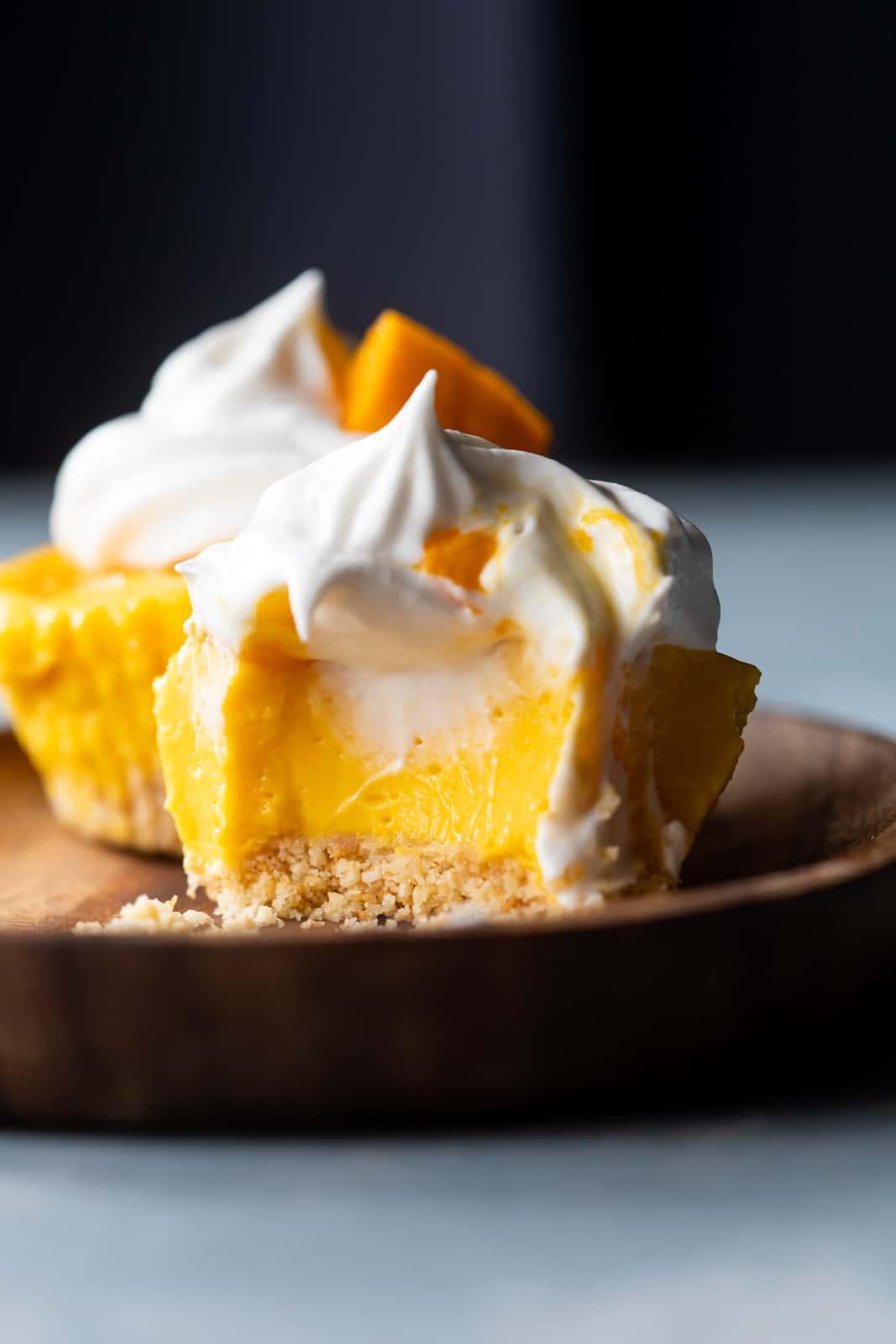 Closeup of a bite takes out of mini mango cheesecakes to show texture