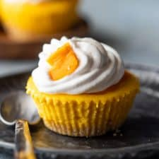 Mini mango cheesecakes served on a plate topped with whipped cream and fresh mangoes