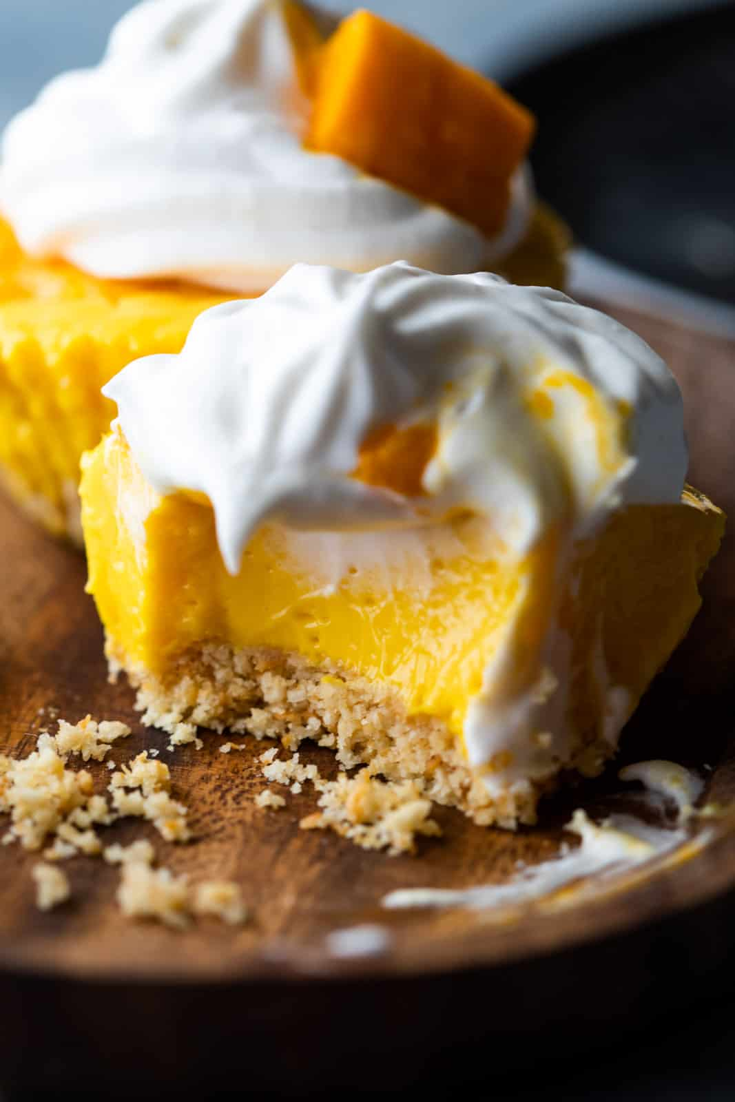 Closeup of a bite takes out of mini mango cheesecakes to show texture