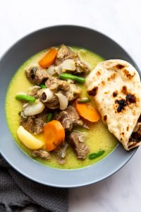 Mutton stew with coconut served in a bowl with naan bread