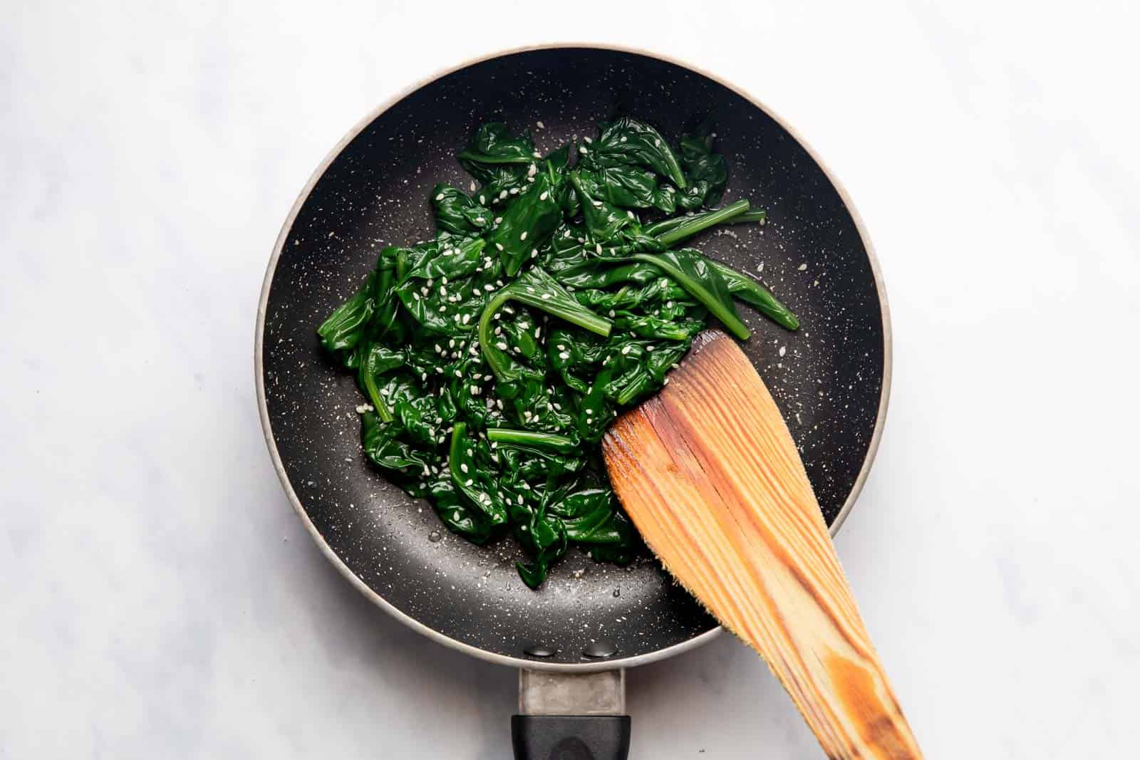 Sauteed Spinach in a pan topped with sesame seeds