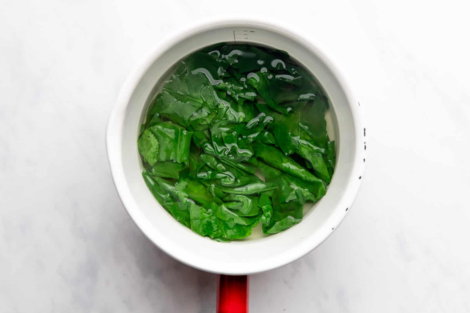 Spinach blanched in hot water in a saucepan