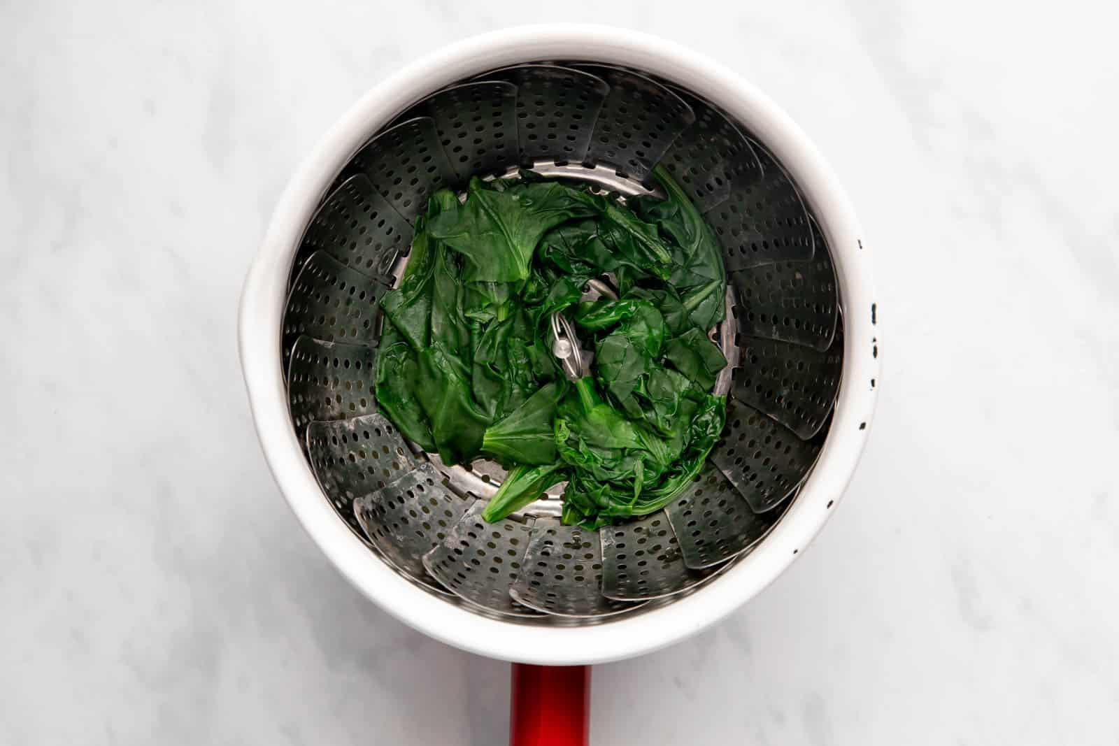 Steaming spinach in a steamer basket till it wilts