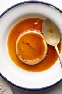 Closeup of coconut caramel custard served on a white plate with a blue edging and a spoon