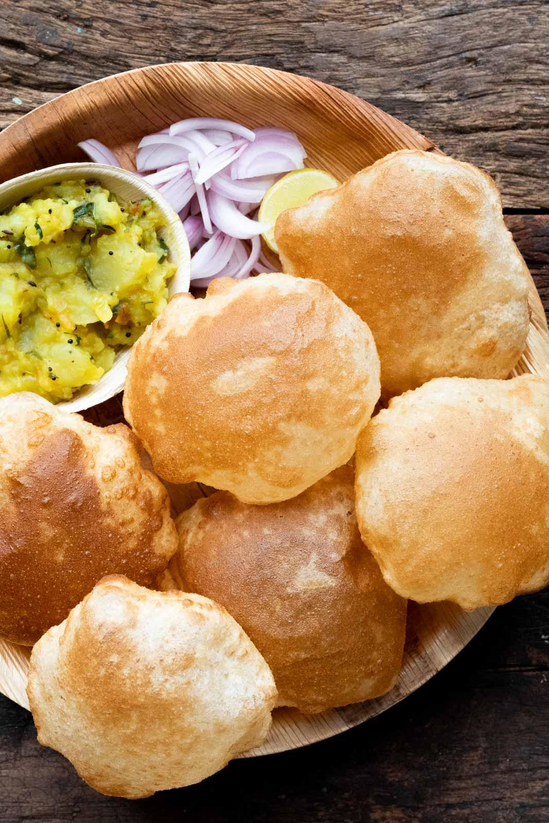 Pooris served on a plate with aloo bhaji, onions