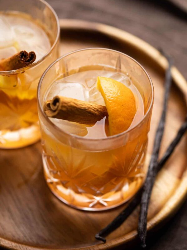 A glass of vanilla cinnamon old fashioned on a tray with vanilla beans on the side