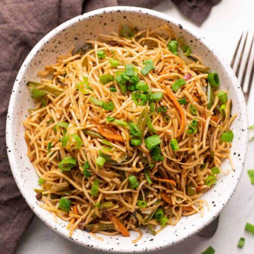 Vegetable hakka noodles served in a white speckled bowl
