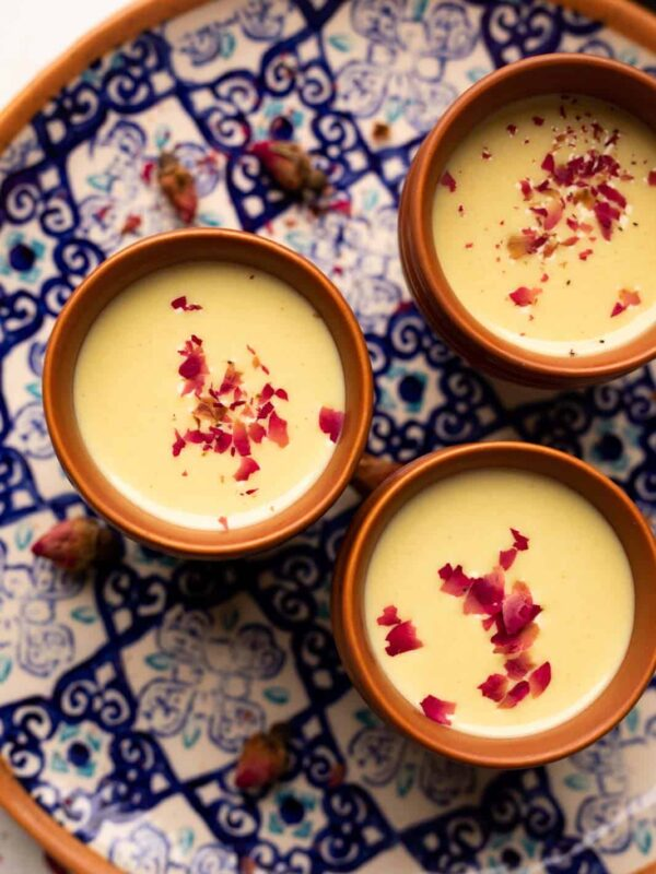 Thandai served in three mud glasses served on a colourful blue plate with rose petals on top
