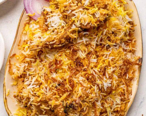 Mutton biryani served on a platter with sliced onions, raita and mirchi salan