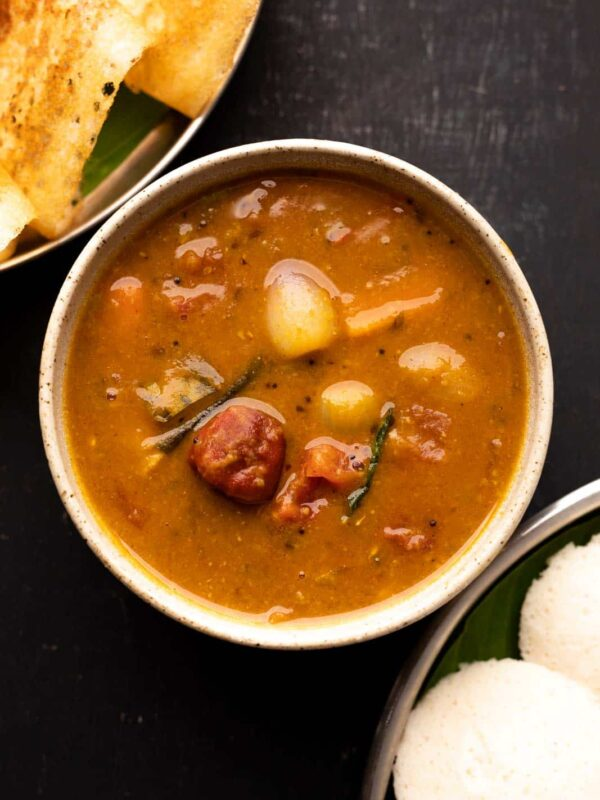 Vegetable sambar served in a brown bowl with a stack of idlis and dosas on the side