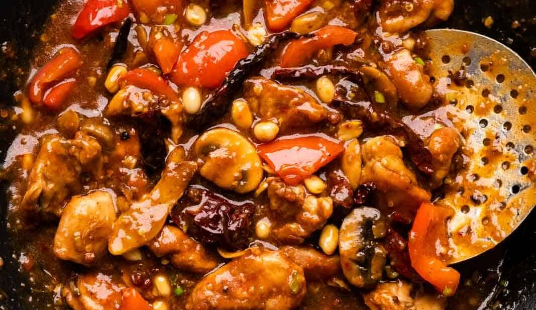 Kung Pao chicken pictures in the wok that it was cooked in with a skimmer