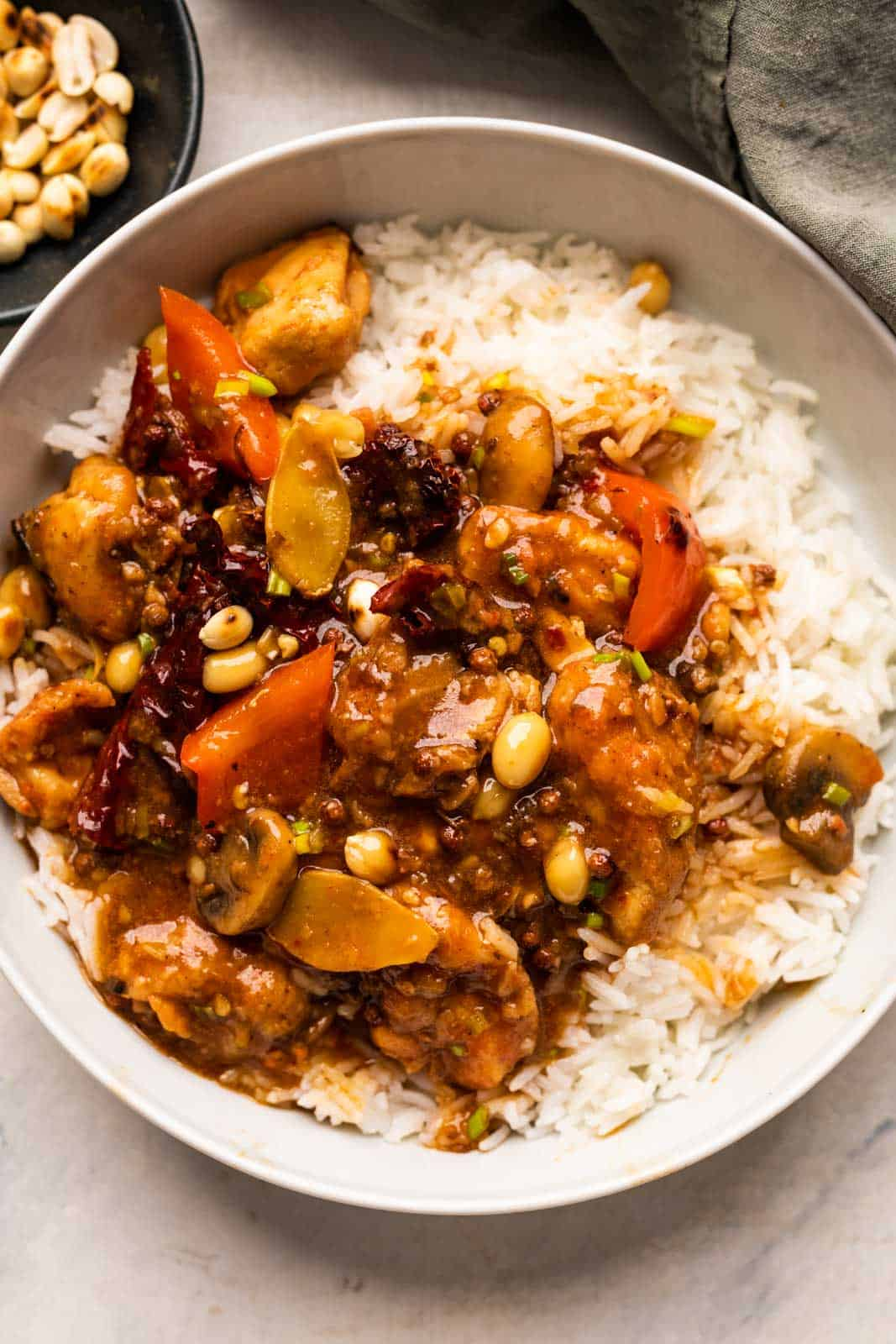 Kung Pao Chicken served over rice in a bowl with peanuts on the side