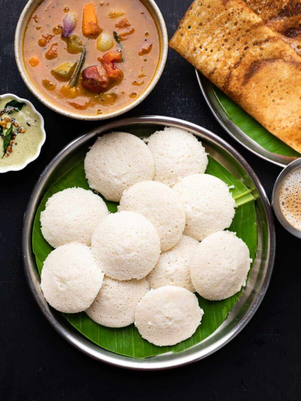 A picture of soft idlis stacked on top of each other on a banana leaf lined plate with dosas, chutney and sambar on the side