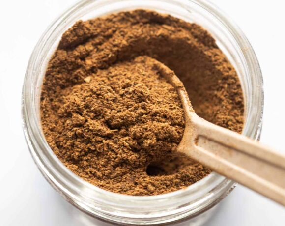 Garam Masala pictured in a glass jar used for storage with a spoon in it