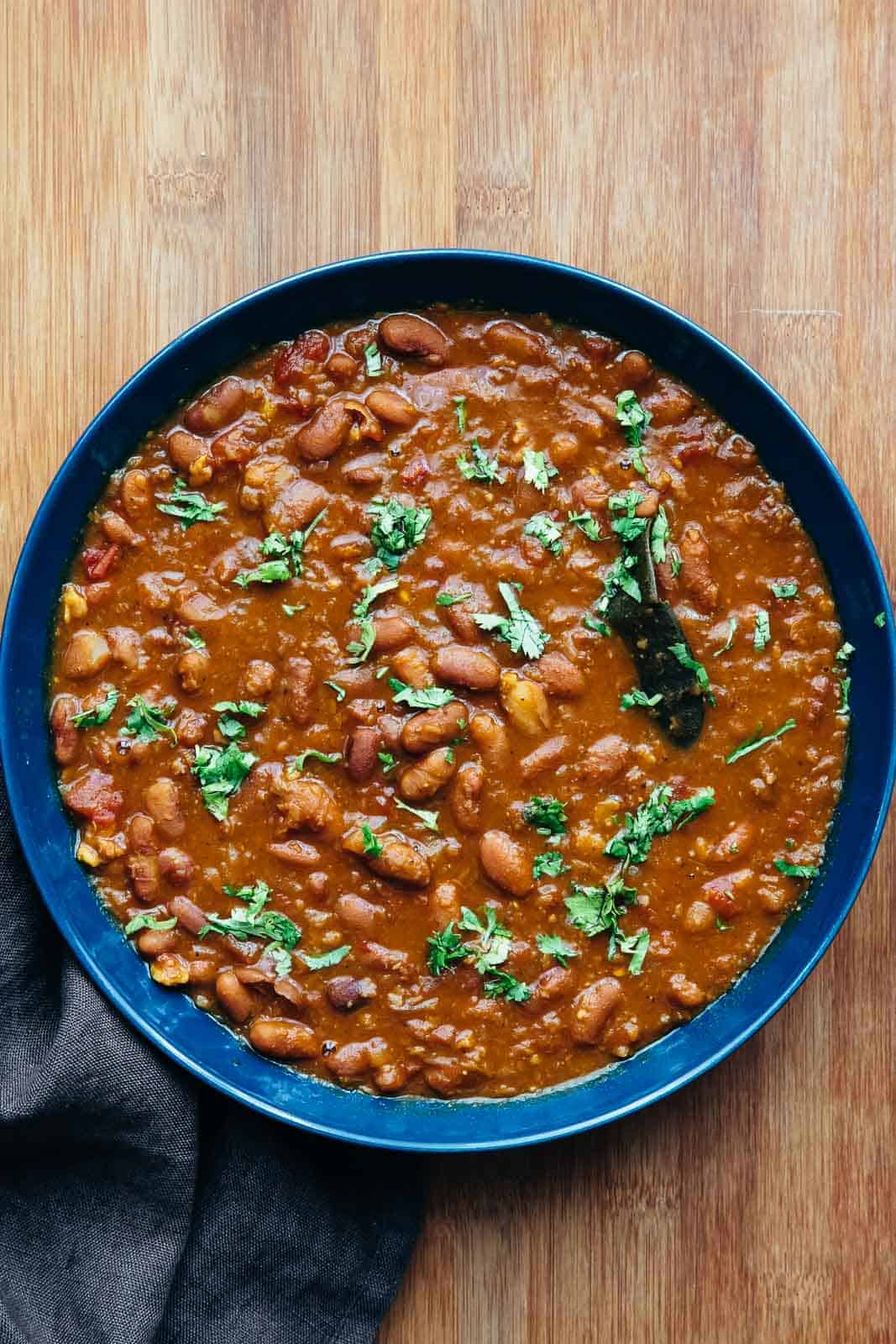Rajma Masala served in a blue bowl with chopped coriander sprinkled over