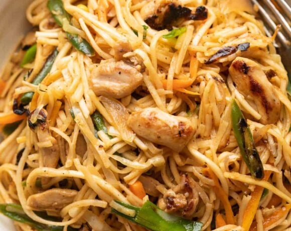 Chicken Chow mein served in a white bowl with a fork on the side