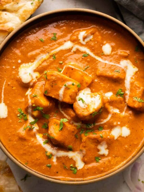 Paneer Butter Masala served in a brown bowl with naan and onions on the side